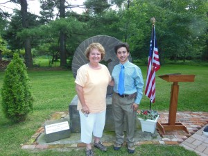 Jean Rounds, Museum Official Photographer, and Col. Nahorn, Museum Director pose for a photo in front of the Shupe grist stone.