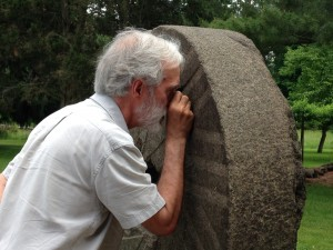 Dr. Hannibal studies the make up of the stone with a hand lens.  It is a granite, which originated from Canada and was pushed here during the last Ice Age.