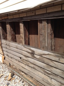 Original clapboard wood siding is exposed on the building.