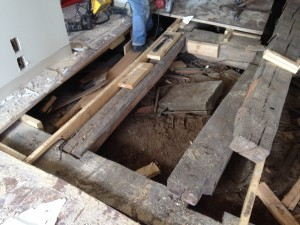 After newer floors were removed, this revealed original hand-hewn beams during exploratory and salvage efforts.